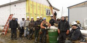 Alaska weatherization workers standing at an energy efficiency job